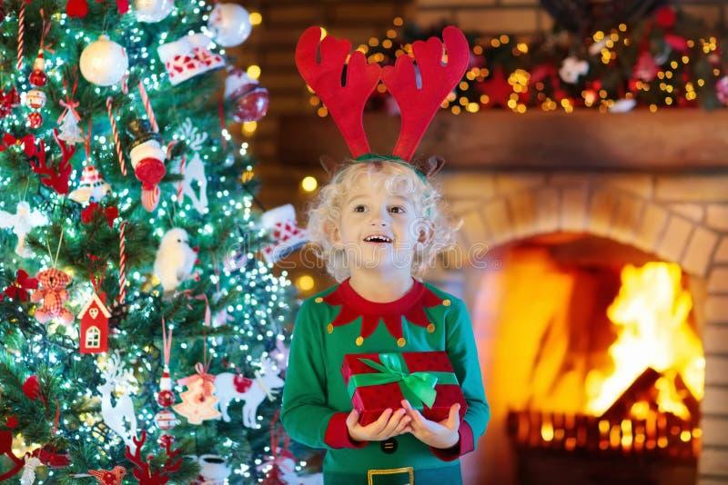 Niño en el árbol de navidad y la chimenea el víspera de Navidad imágenes de archivo libres de regalías