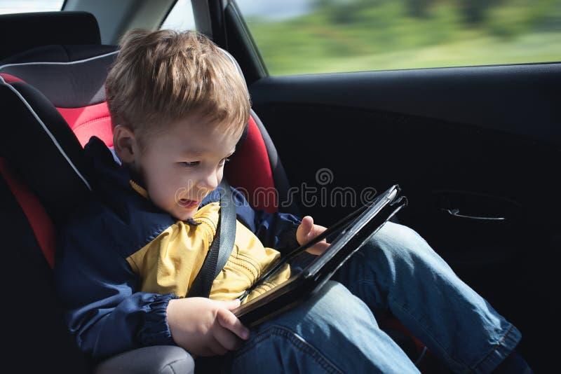 Niño en el coche con la tableta foto de archivo libre de regalías