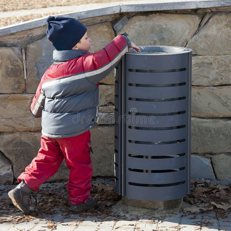 Niño en el compartimiento de los desperdicios fotos de archivo libres de regalías