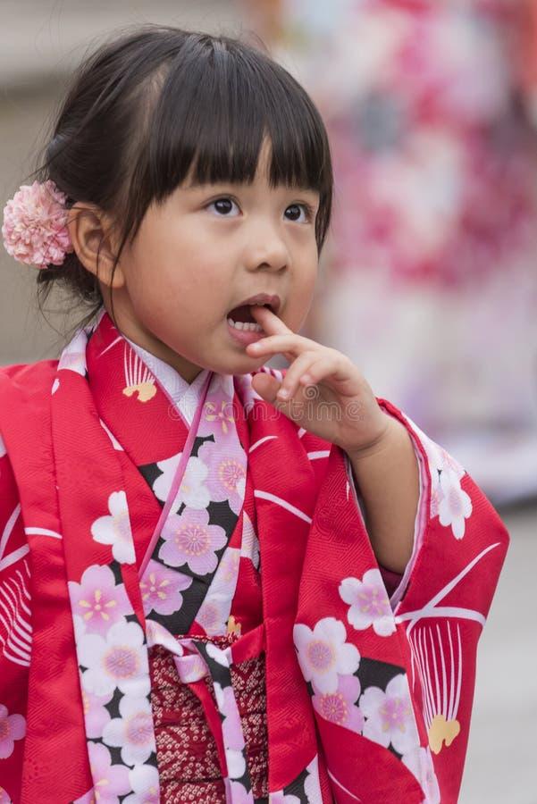 Niño en el kimono rojo que mira Asakusa pensativo foto de archivo
