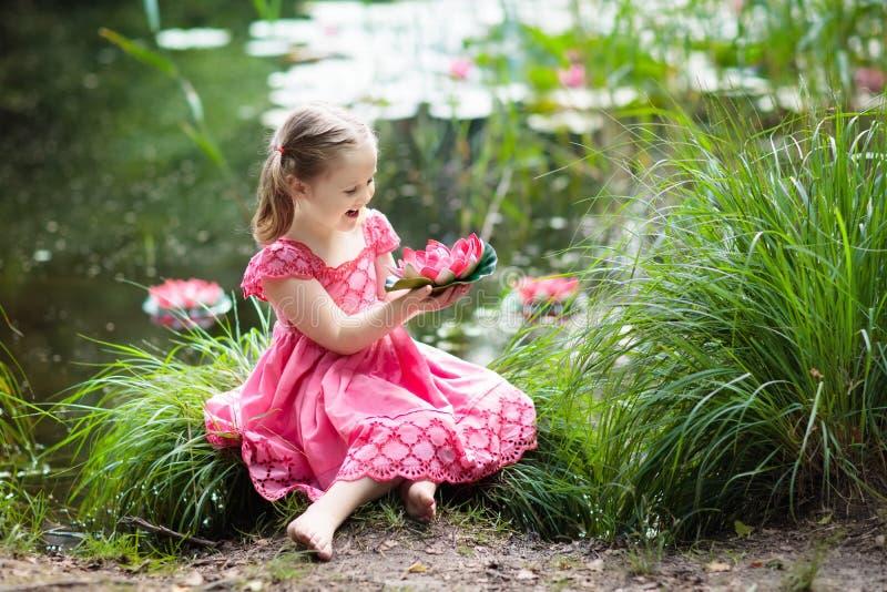 Niño en el lago con las flores del lirio de agua fotos de archivo