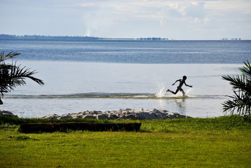 Niño en el lago Victoria imagenes de archivo
