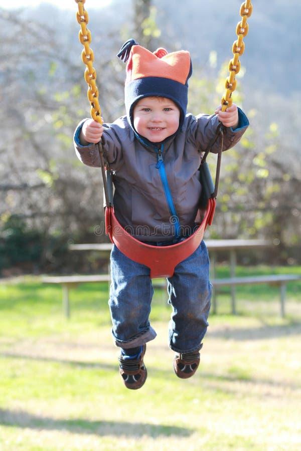 Niño en el oscilación en un patio fotografía de archivo
