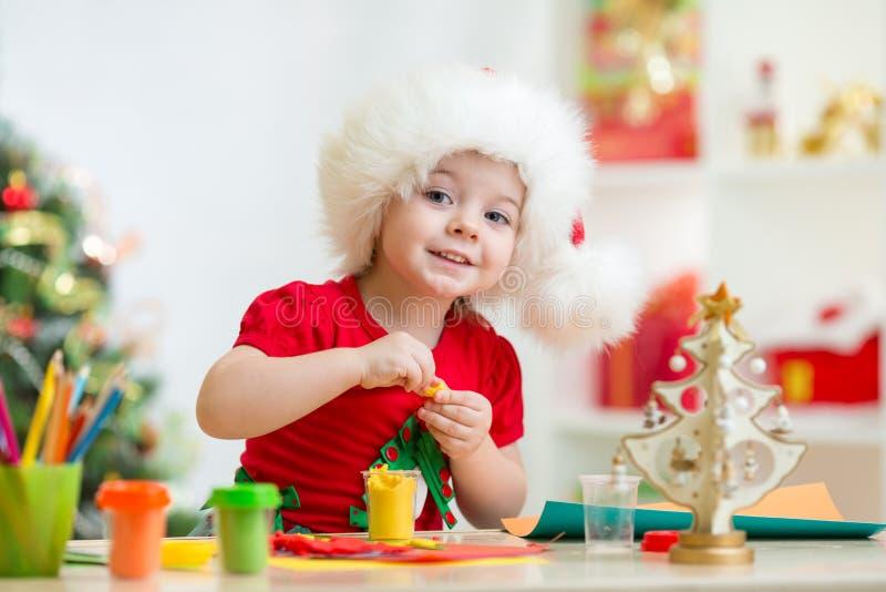 Niño en el sombrero de Papá Noel que hace el árbol de navidad de imagen de archivo libre de regalías