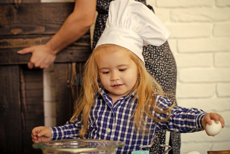 Niño en el sombrero del cocinero que rompe el huevo del cuenco en cocina fotos de archivo libres de regalías