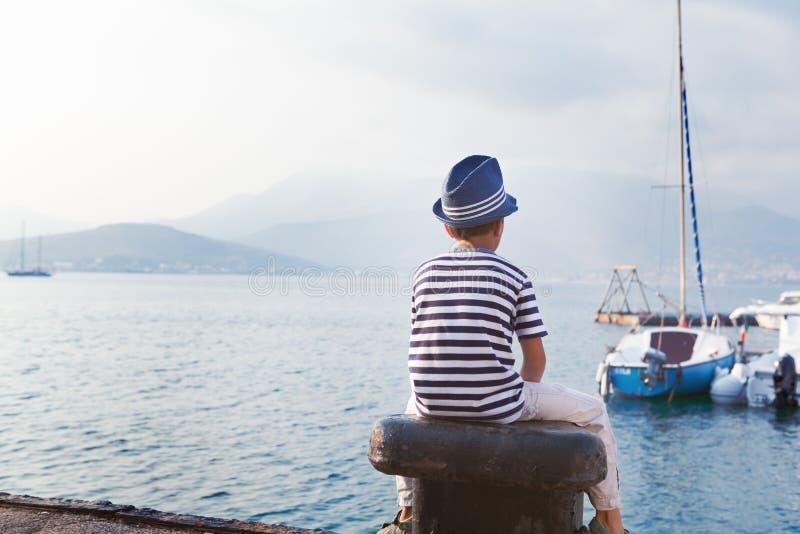 Niño en el sombrero que mira el mar y la nave fotos de archivo