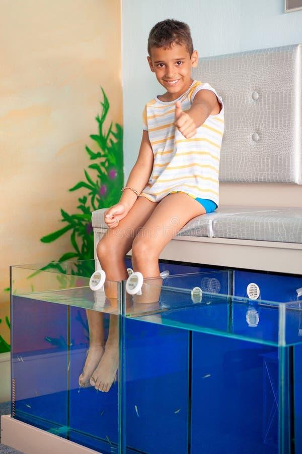Niño en el tratamiento del cuidado de piel de la pedicura de los pies del balneario de los pescados, con los fis foto de archivo