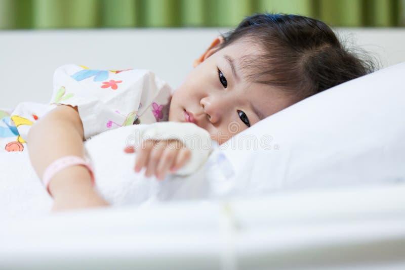 Niño en hospital, asiático salino de la enfermedad del intravenoso (iv) a mano foto de archivo