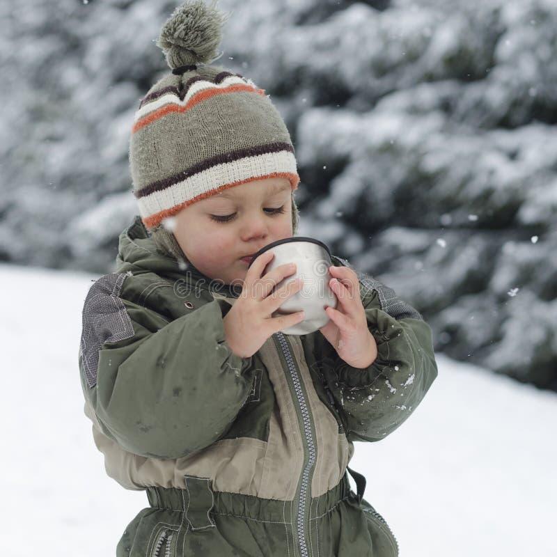 Niño en invierno que bebe té caliente fotos de archivo