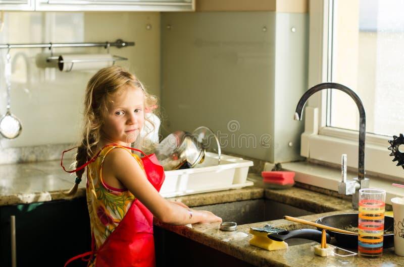 Niño en la ayuda de la cocina foto de archivo