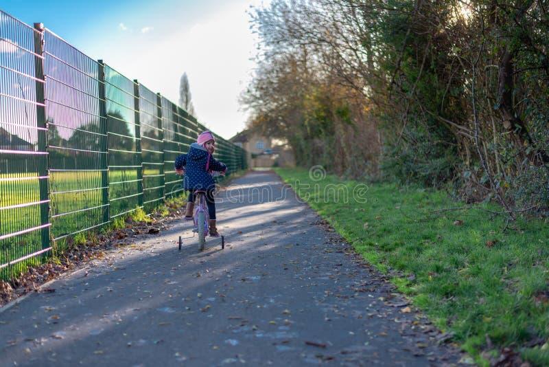 Niño en la bici que mira detrás y que sonríe en la trayectoria por la cerca imagen de archivo libre de regalías