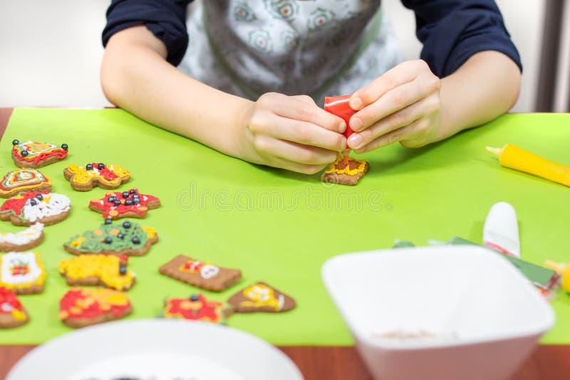 Niño en la cocina Adornamiento de las galletas con la formación de hielo colorida Las manos del niño exprimen helar en amarillo imagen de archivo