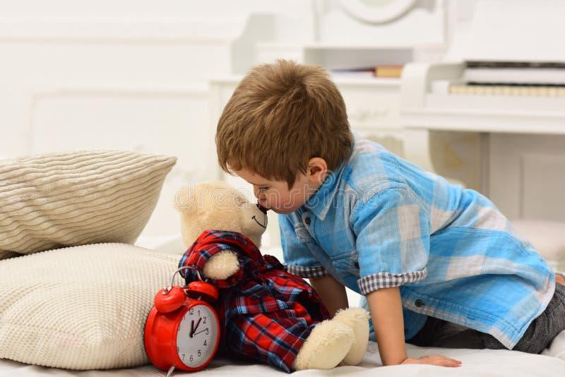 Niño en la habitación besando juguete en la nariz. Concepto de buena noche. Niño con cara feliz pone juguete favorito en la cam foto de archivo libre de regalías