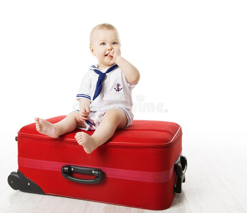 Niño en la maleta del viaje, bebé que se sienta en el equipaje rojo, niño de un año en blanco imagen de archivo