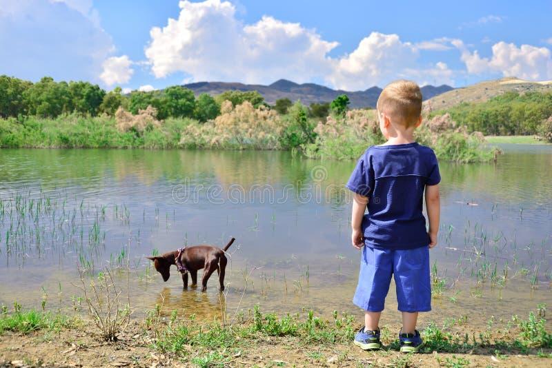 Niño en la orilla del pozzillo del lago, Sicilia imagenes de archivo