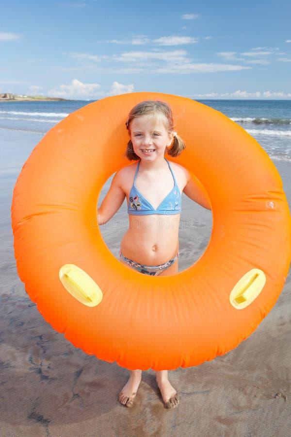 Niño en la playa con el anillo de goma gigante fotos de archivo