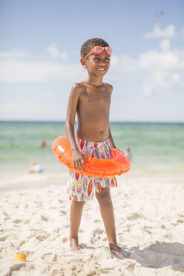 Niño en la playa en traje de baño fotos de archivo libres de regalías