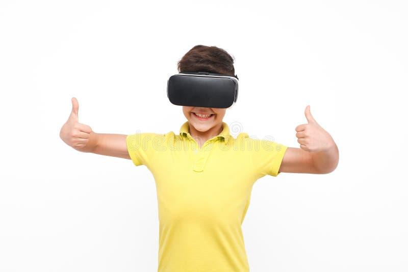 Niño en las auriculares de VR que muestran los pulgares para arriba imagenes de archivo