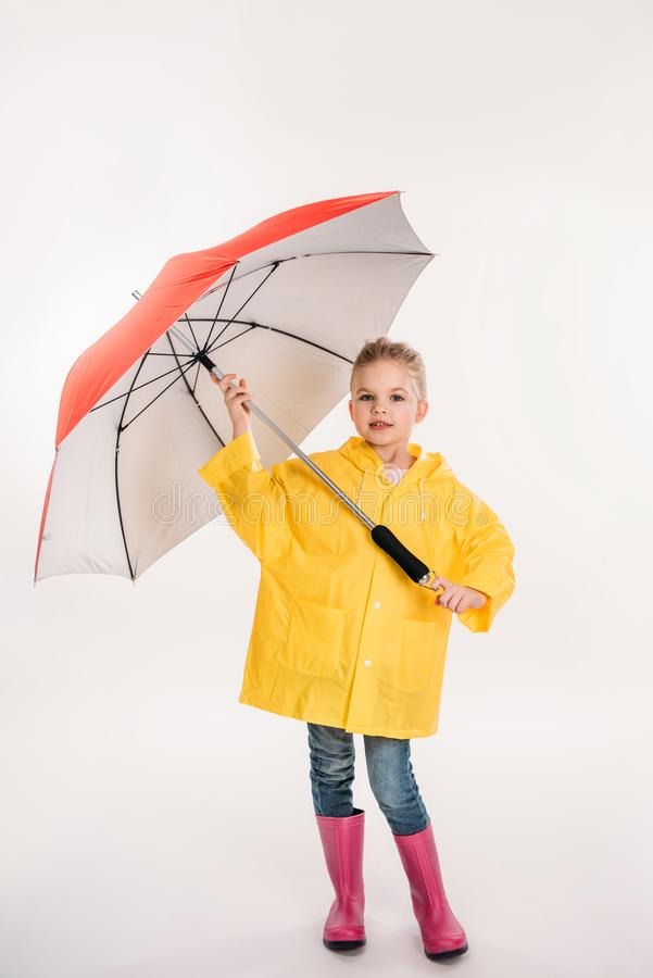 niño en las botas de goma, impermeable amarillo del preescolar con el paraguas, fotografía de archivo