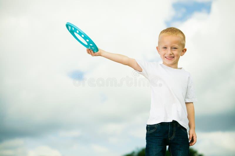 Niño en niño del patio en el muchacho de la acción que juega con el disco volador imagenes de archivo