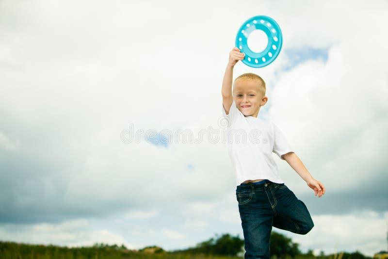 Niño en niño del patio en el muchacho de la acción que juega con el disco volador imagen de archivo
