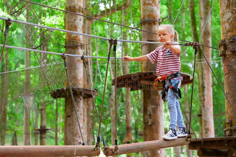 Niño en obstáculo del paso del arnés de seguridad en parque de la cuerda de la aventura imagen de archivo libre de regalías