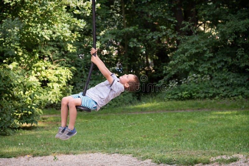 Niño en parque en una línea oscilación de la cremallera imagen de archivo