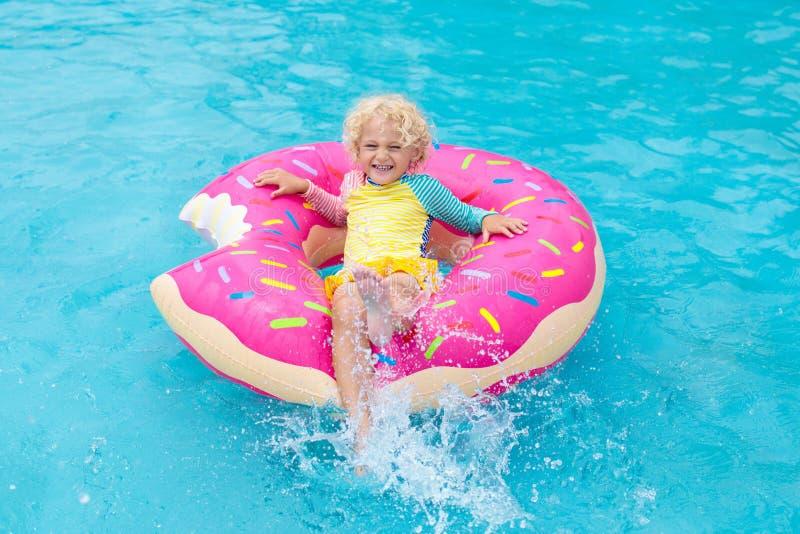 Niño en piscina en el flotador del buñuelo fotos de archivo