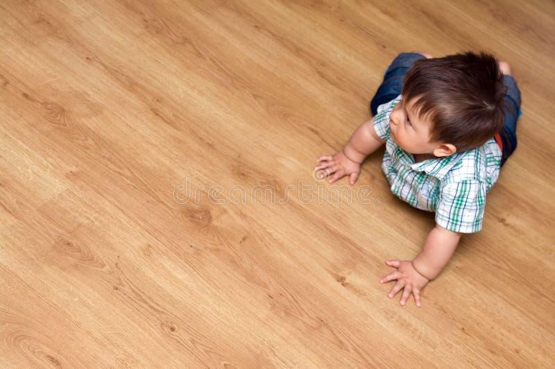 Niño en suelo laminado imagenes de archivo