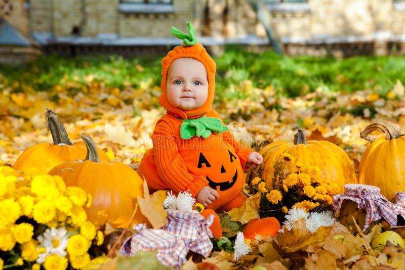 Niño en traje de la calabaza en el fondo de las hojas de otoño imágenes de archivo libres de regalías