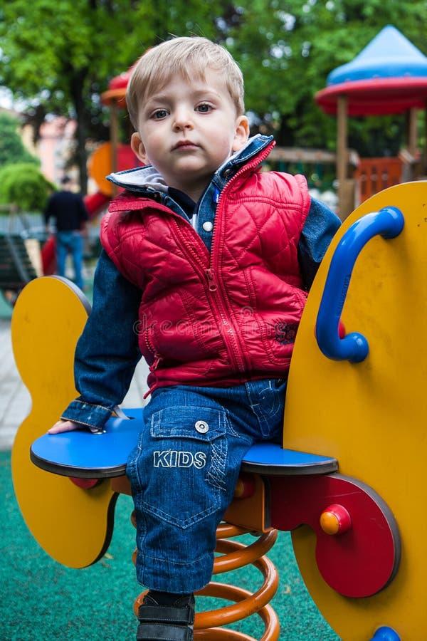Niño en un caballo de la primavera foto de archivo