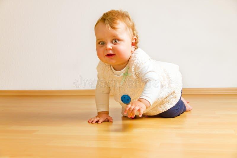 Niño en un piso de entarimado imagenes de archivo