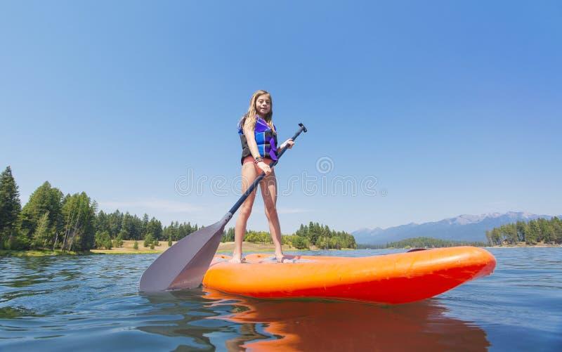Niño en un soporte encima del tablero de paleta en un lago hermoso mountain foto de archivo