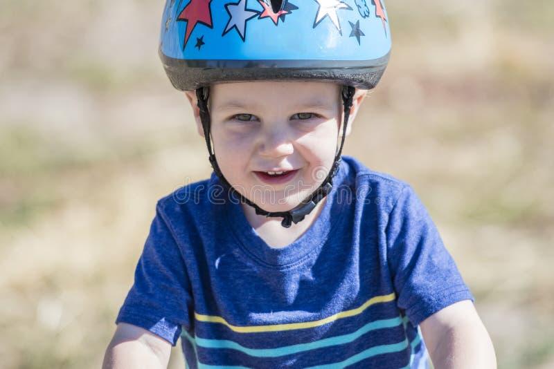 Niño en una bici de Strider en un casco que lleva de la pista de tierra foto de archivo