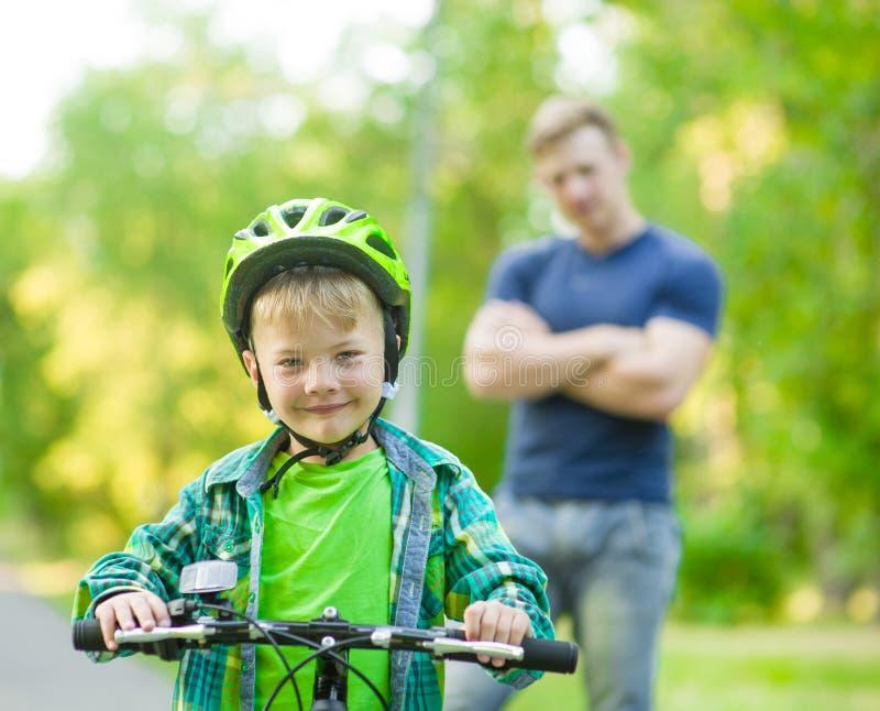 Niño en una bicicleta con el padre en el parque fotografía de archivo