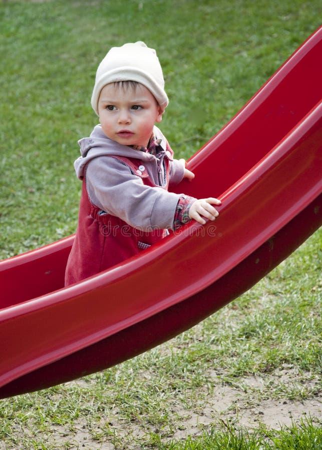 Niño en una diapositiva imagenes de archivo