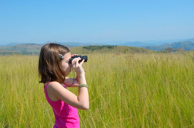 Niño en viaje del safari en África, muchacha que mira a la sabana con los prismáticos fotografía de archivo