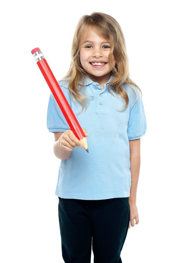 Niño encantador con el pelo hermoso que sostiene el lápiz rojo fotos de archivo libres de regalías