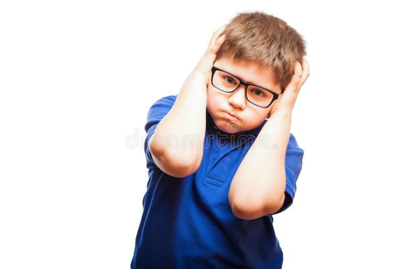 Niño enfadado que cubre sus oídos imagenes de archivo