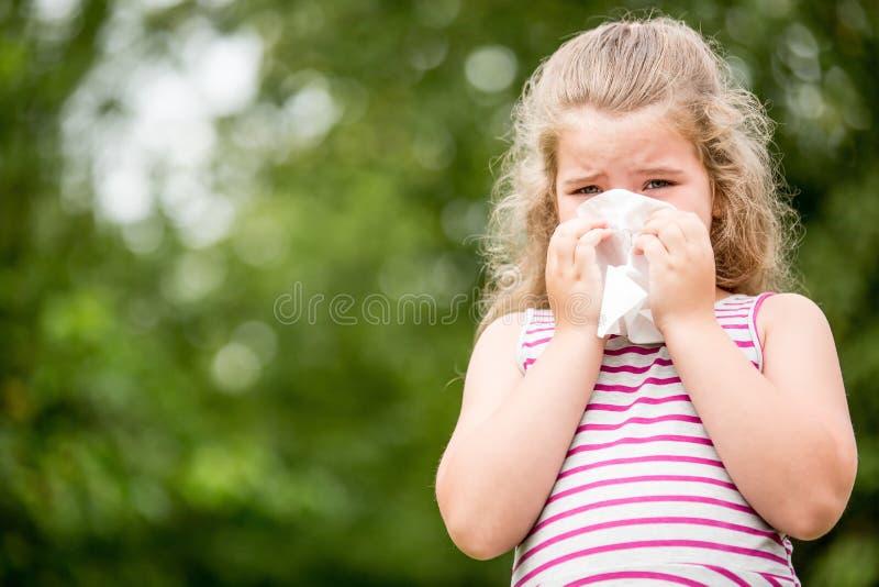 Niño enfermo con estornudos de la gripe foto de archivo