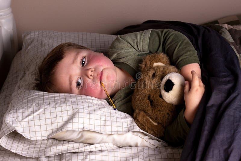 Niño enfermo con fiebre fotografía de archivo