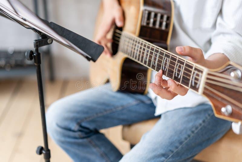 Niño enfocado tocando su melodía favorita en guitarra acústica fotos de archivo