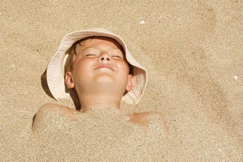 Niño enterrado en la arena fotos de archivo