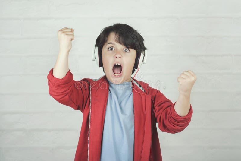 Niño eufórico en auriculares que escucha la música imagen de archivo