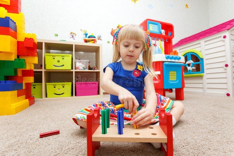 Niño fascinado que juega con los palillos de madera en guardería foto de archivo