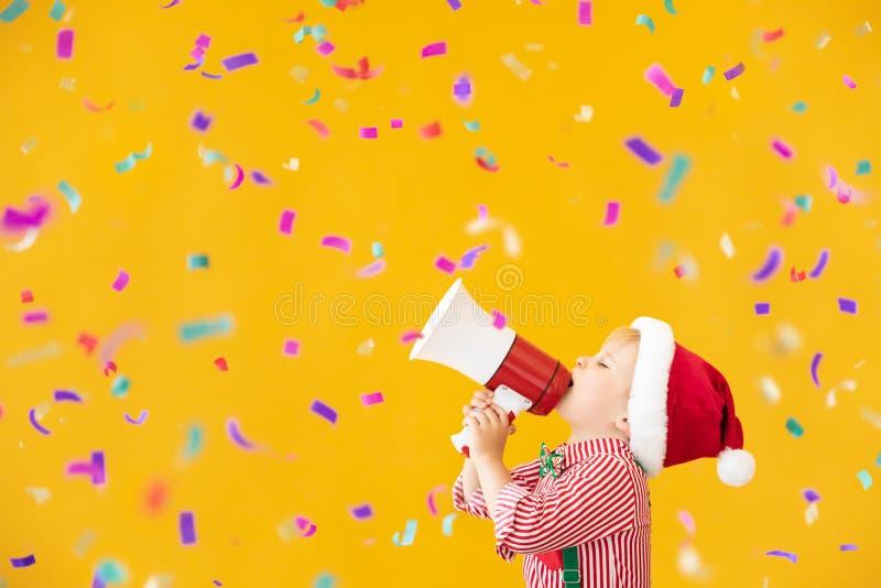 Niño feliz con disfraz de Papá Noel hablando por megáfono foto de archivo libre de regalías
