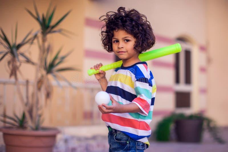 Niño feliz con el equipo de béisbol del juguete al aire libre fotos de archivo