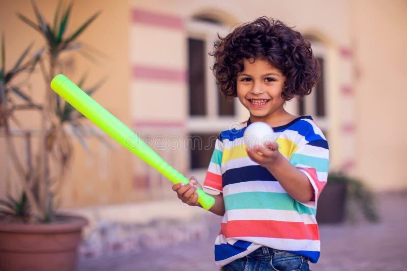 Niño feliz con el equipo de béisbol del juguete al aire libre fotografía de archivo