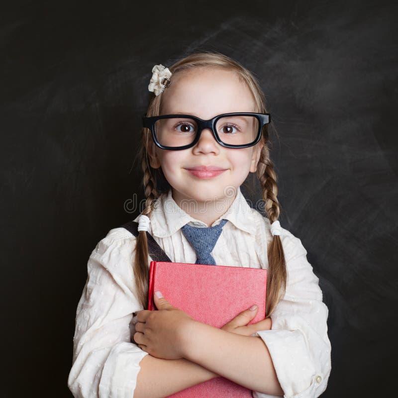 Niño feliz con el libro en fondo de la pizarra De nuevo a escuela, vector foto de archivo libre de regalías
