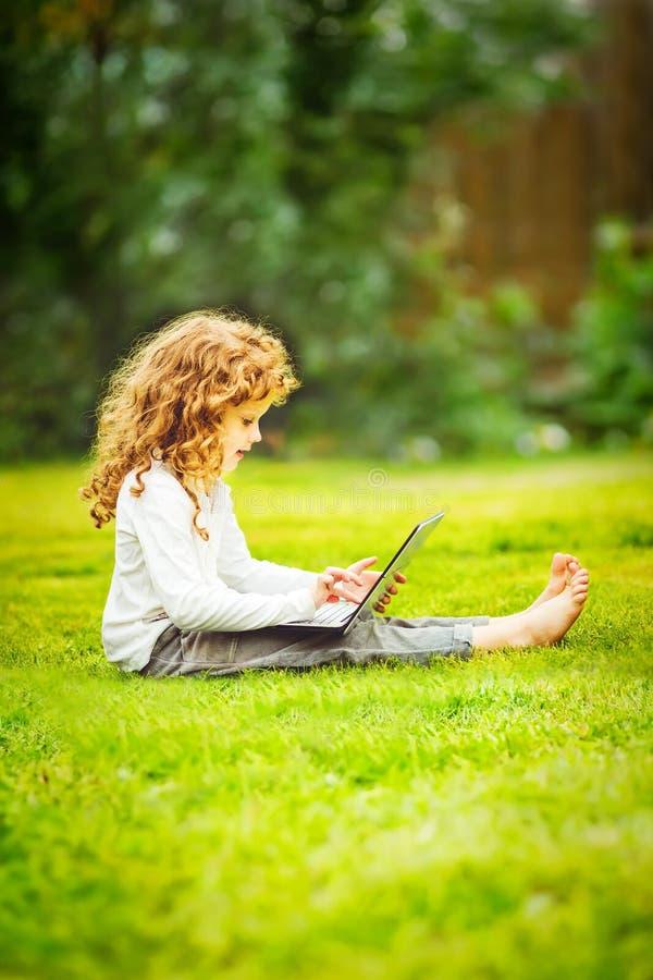 Niño feliz con el ordenador portátil que se sienta en la hierba foto de archivo libre de regalías